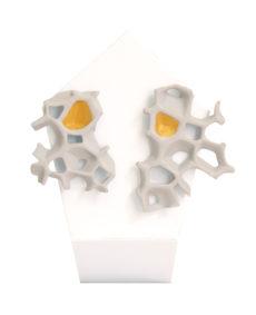 pendientes asimetricos espina blanco y oro de BaRock jewelry sobre expositor