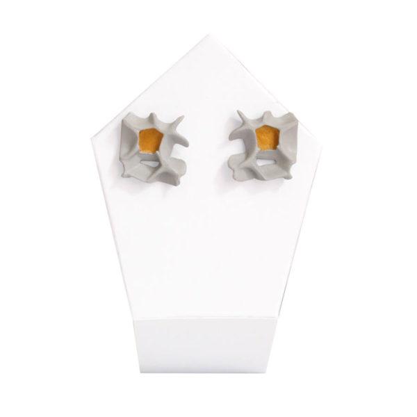 pendientes originales pequeños espina blanco y oro de BaRock jewelry sobre expositor