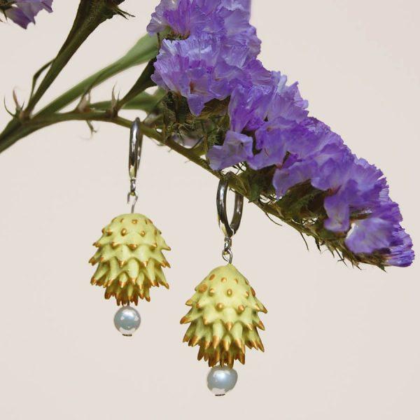 Pendientes amarillos de BaRock jewelry frente sobre flor lila y fondo amarillo