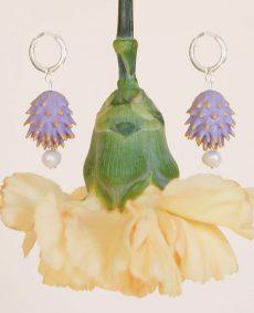Pendientes lilas de BaRock jewelry frente sobre flor amarilla y fondo amarillo