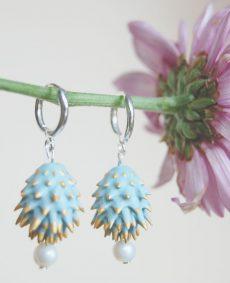 Pendientes azules de BaRock jewelry frente sobre flor lila y fondo amarillo