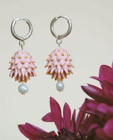Pendientes Bardana rosas de BaRock jewelry frente sobre flor granate y fondo amarillo