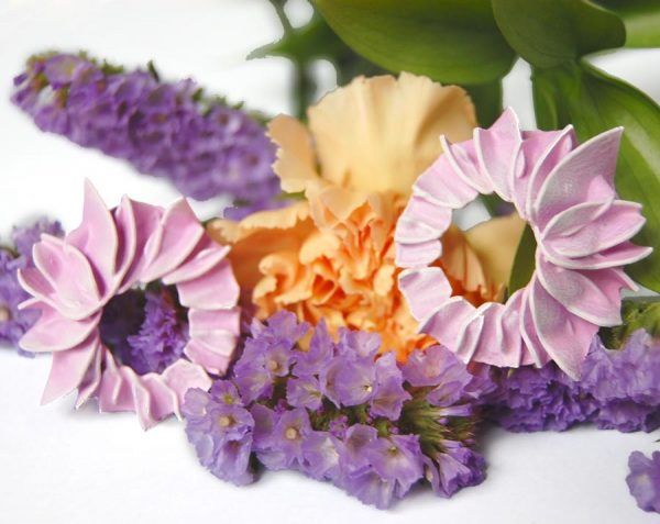 Pendientes pétalos rosas grandes de BaRock jewelry sobre flores lilas, granates y amarillas en fondo blanco.