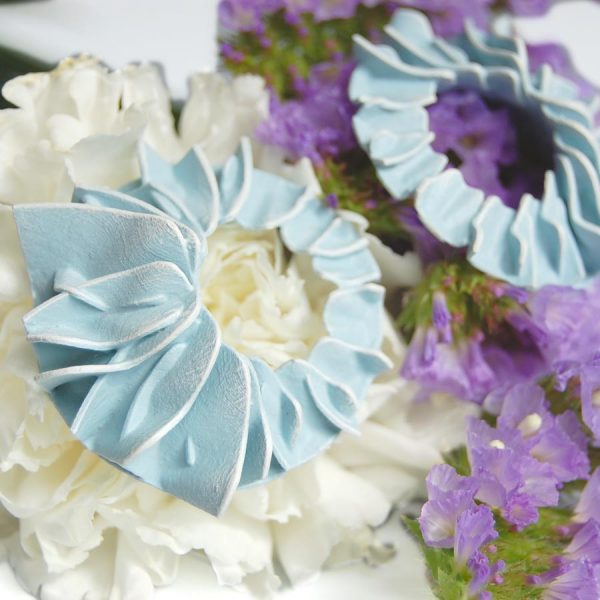 Pendientes pétalos azules grandes de BaRock jewelry sobre flores blancas y lilas