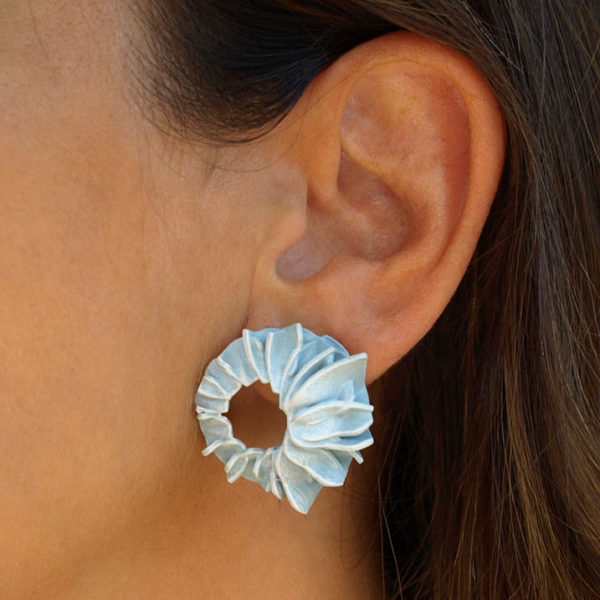 Pendientes lorak azules pequeños de BaRock jewelry en oreja de modelo