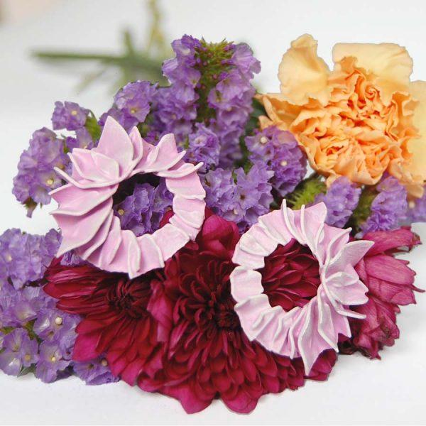 Pendientes pétalos arosas pequeñoss de BaRock jewelry sobre flores granates, amarillas y lilas.