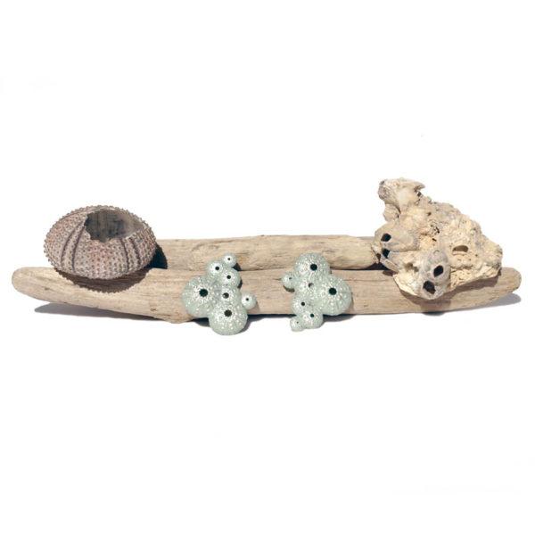 pendientes asimétricos triku de BaRock jewelry sobre palos con caparazón de erizo de mar y piedra