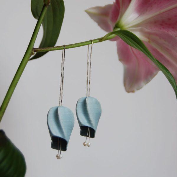 Pendientes abiluria azules de la colección lorak sobre flor en fondo gris