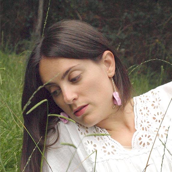 Pendientes abiluria rosas de la colección lorak en modelo con vestido blanco y fondo verde