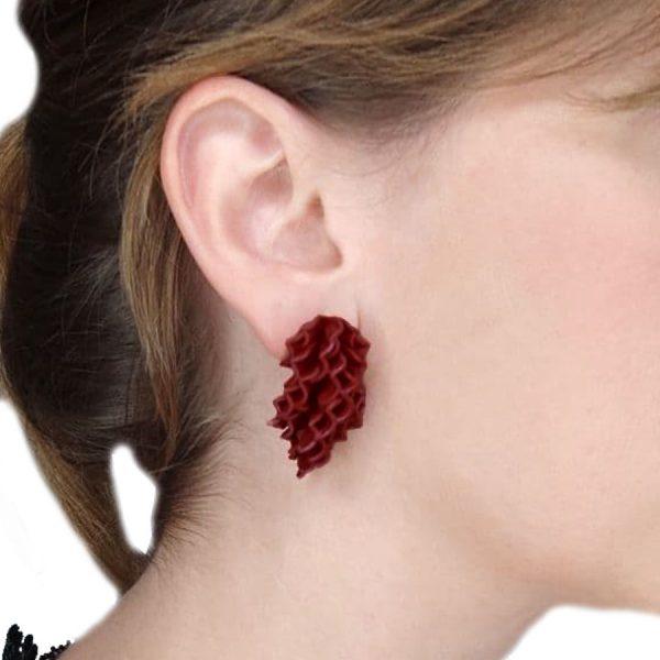 Pendientes grandes petalos rojos en cascada en modelo, detalle de oreja derecha.