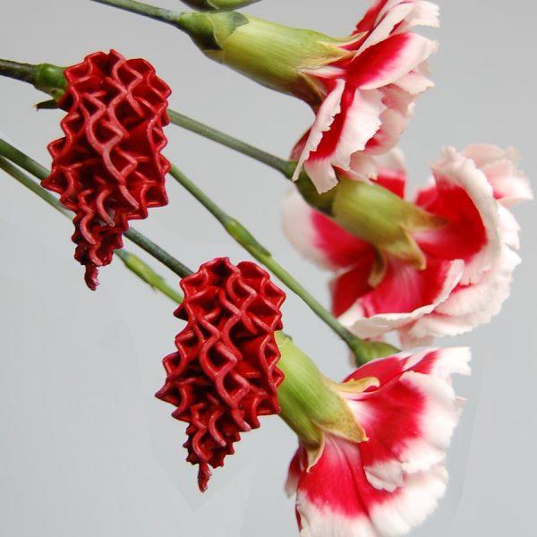 Pendientes petalos rojos en cascada sobre claveles rojos y blancos y fondo gris