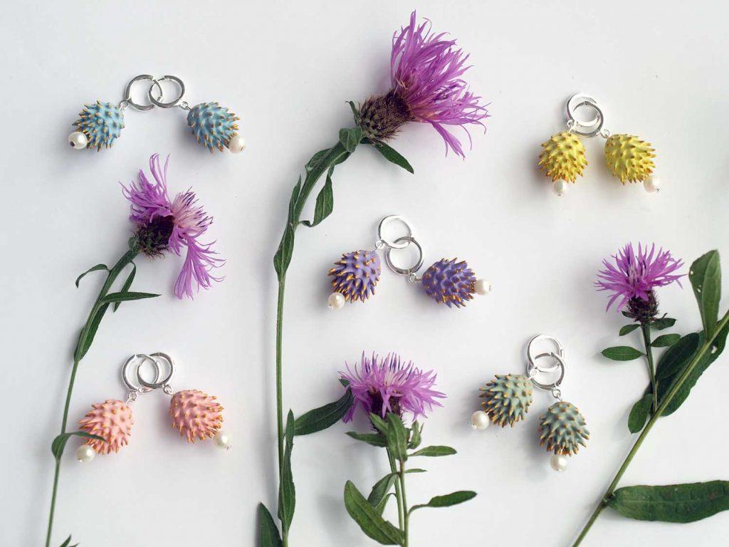 Pendiente bardada en lila, amarillo, azul, verde y rosa con flores de bardana sobre fondo blanco