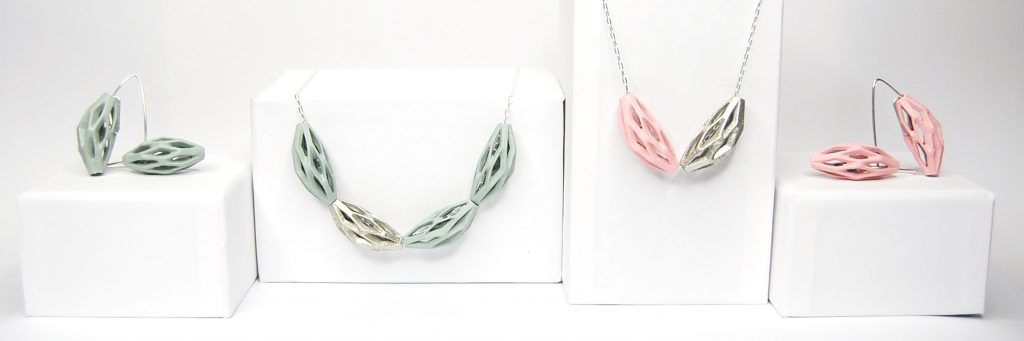 colección belaki de BaRock jewelry, collares y pendientes en verde, rosa y plata sobre expositor blanco