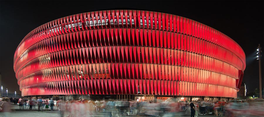 Foto nocturan del estadio San Mames de Bilbao iluminado en rojo