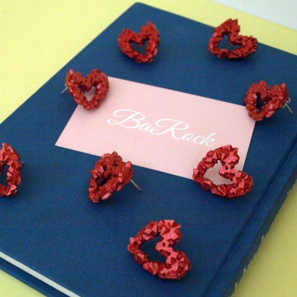 pendientes harria corazón rojos sobre libro azul y tarjeta