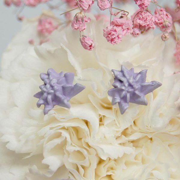 pendientes armeria lilas de la colección lorak sobre clavel blanco y flores rosas y lilas con fondo gris